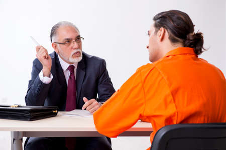 Young captive meeting with advocate in pre-trial detention Stock Photo