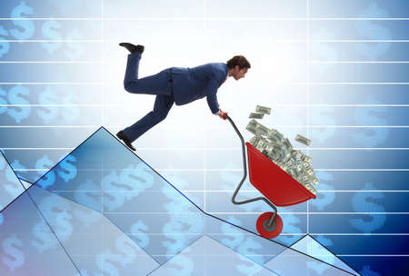 Businessman pushing money wheelbarrow down the chart
