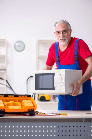 Old male contractor repairing microwave indoors