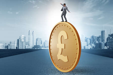 Businessman with giant golden pound coin