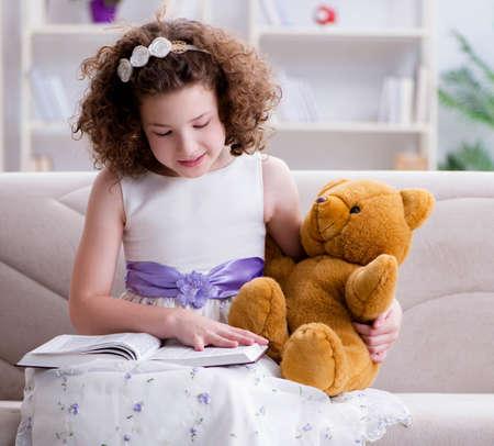 Little pretty girl reading books at home Foto de archivo