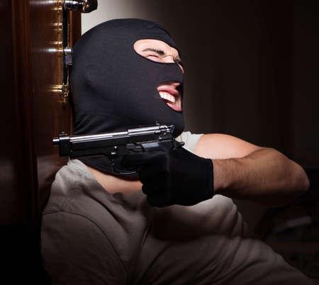 The burglar wearing balaclava mask at crime scene