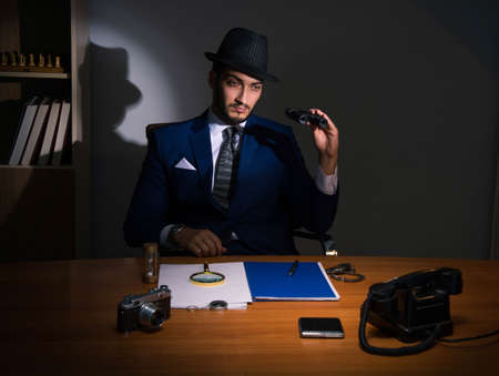 Detective sitting in dark room in vintage concept