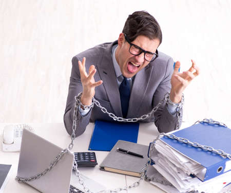 Busy employee chained to his office desk Stock Photo