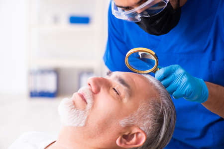 Old man visiting young male doctor in hair transplantation conce