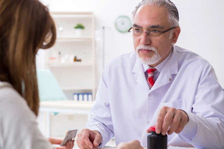 Young woman visiting experienced doctor