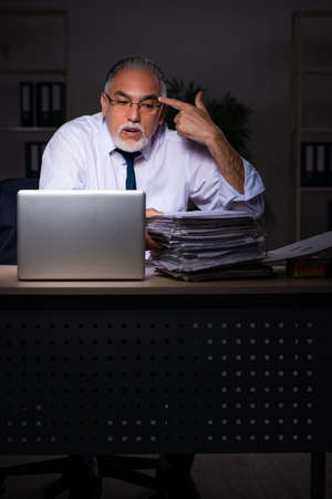 Old male employee working late at workplace Banque d'images - 151453530
