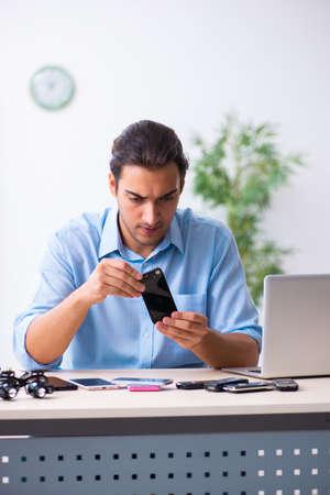Young male technician repairing mobile phone Reklamní fotografie
