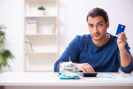 Young man in budget planning concept Banque d'images - 151453584