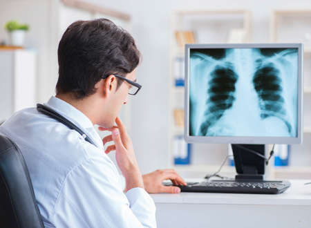 Doctor radiologist looking at x-ray images Imagens
