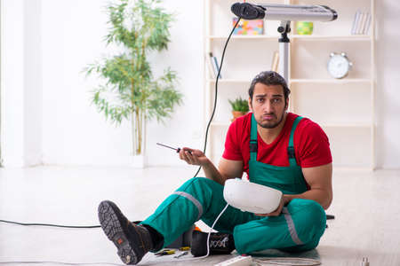 Young male contractor repairing fan heater indoors