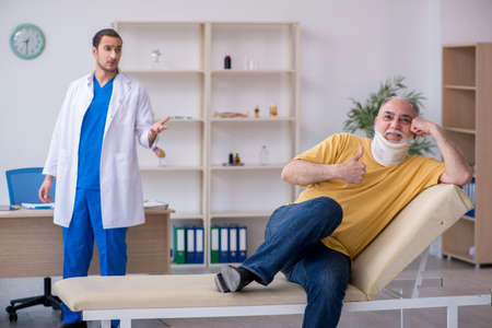 Old neck injured man visiting young male doctor Stock Photo