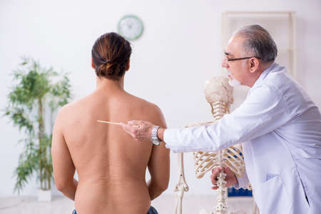 Young back injured man visiting experienced male doctor Standard-Bild