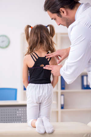 Small girl visiting young male doctor