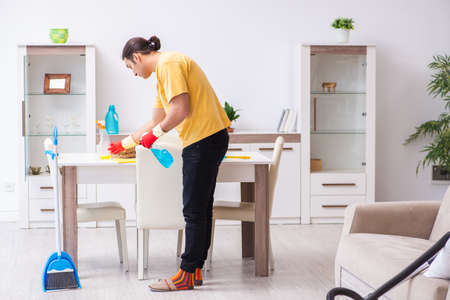 Young male contractor cleaning the house