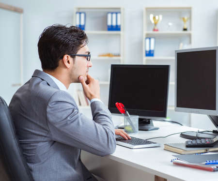 Businessman sitting in front of many screens Banco de Imagens