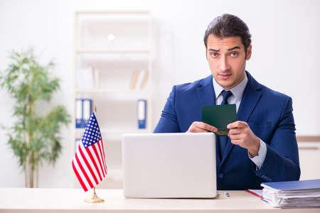 Young man checking passport at USA embassy Foto de archivo