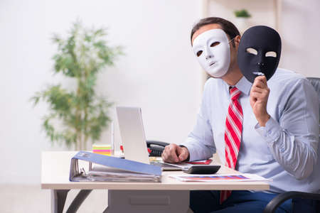 Male employee with mask in hipocrisy concept