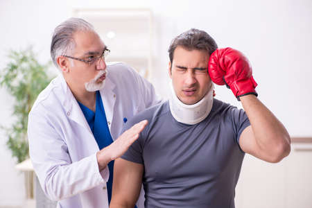 Young injured boxer visiting old doctor traumatologist Standard-Bild