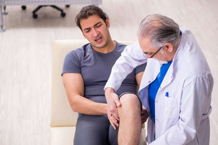 Young male patient visiting old doctor traumatologist