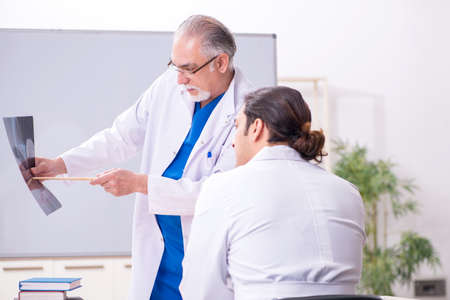 Experienced doctor radiologist teaching young male assistant