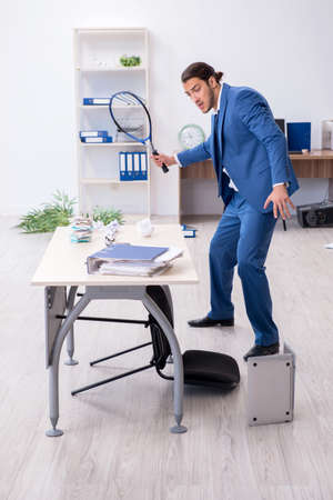 Young male employee playing tennis in the office