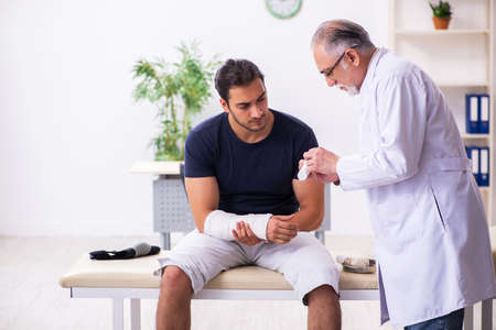 Young injured man visiting experienced male doctor traumatologis