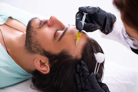 Young man visiting female beautician in hair transplantation con Standard-Bild