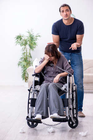Disabled wife and young husband at home Banco de Imagens