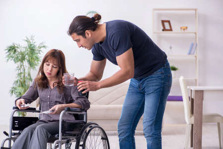 Disabled wife and young husband at home Stockfoto