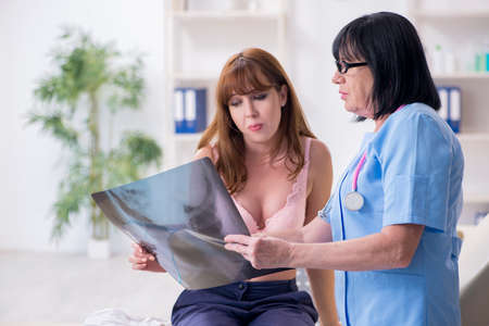 Young woman visiting old doctor oncologist in breast cancer