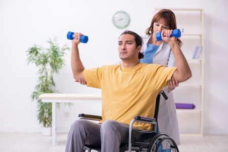 Young male patient in wheel-chair doing physical exercises Stock Photo