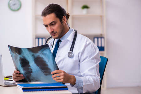 Young male handsome doctor working in the clinic