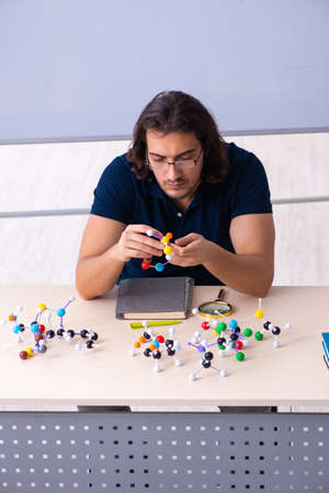 Young male scientist sitting in the classroom