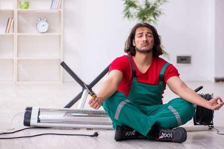 Young male contractor repairing heater indoors