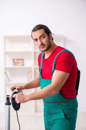 Young male contractor repairing heater indoors Stockfoto