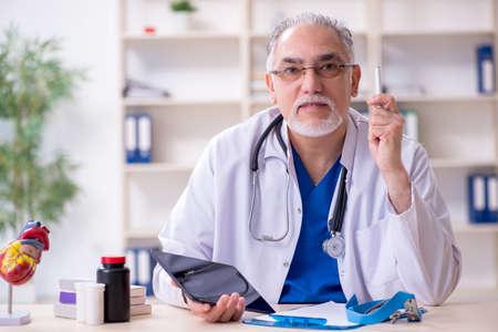 Old male doctor cardiologist in telehealth concept Archivio Fotografico