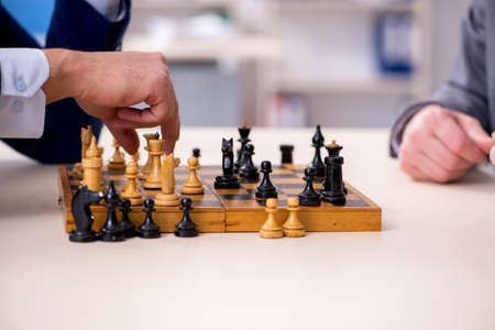 Two businessmen playing chess in the office Banque d'images