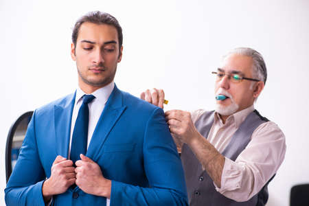 Young businessman visiting old male tailor