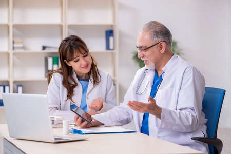 Old male doctor radiologist and his young female assistant in th