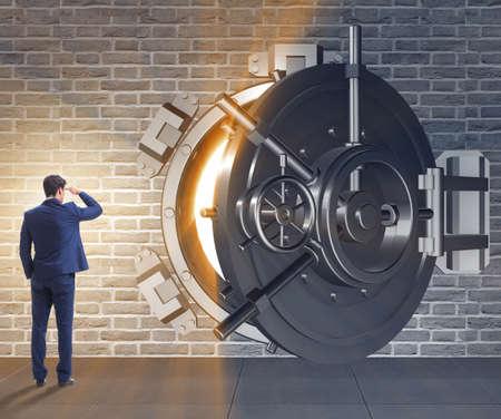 Businessman in front of banking vault door Imagens
