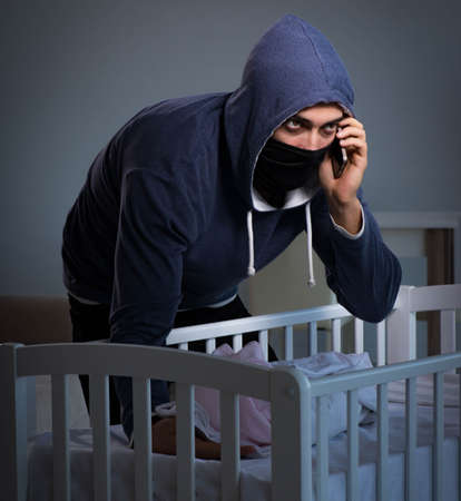 Criminal stealing baby in human child traficking concept