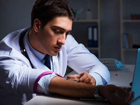 Doctor drug addict staying late on hospital Imagens