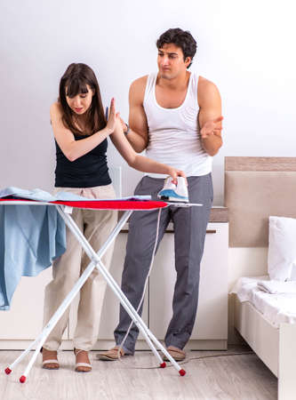 Young woman doing ironing for her husband Stock Photo