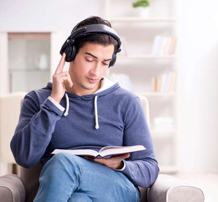 Young man reading book and listening to audio book Stockfoto