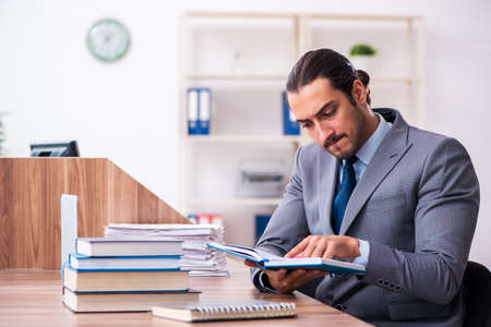 Young male businessman reading books at workplace Imagens