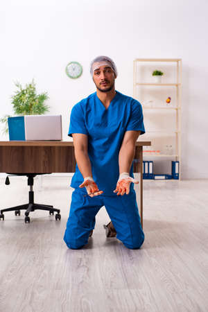 Young male doctor surgeon in fatal negligence concept