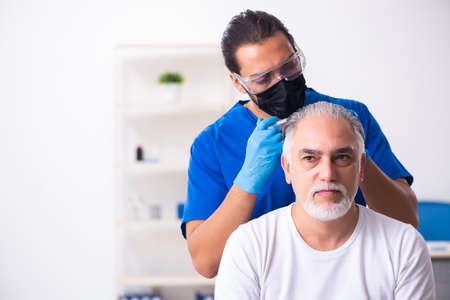 Old man visiting young male doctor in hair transplantation conce Standard-Bild