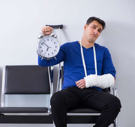 Desperate man waiting for his appointment in hospital with broke Imagens