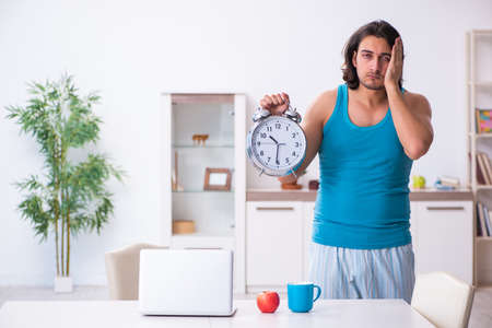 Young man waking up at home